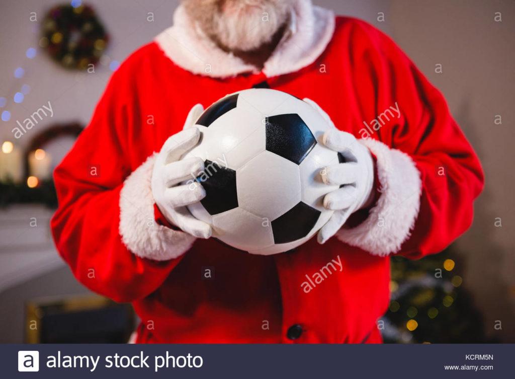 mid-section-of-santa-claus-holding-a-football-KCRM5N