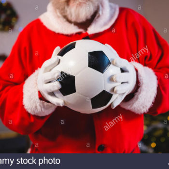 mid-section-of-santa-claus-holding-a-football-KCRM5N
